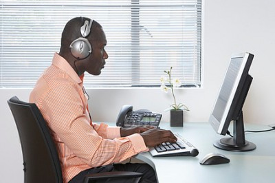 Young man using computer at desk, wearing headphones