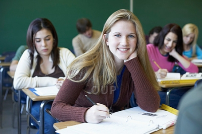 Young woman working and smiling in classroom
