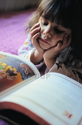 Six year old girl reading on the floor