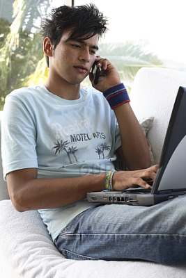 Teenage boy on laptop and phone