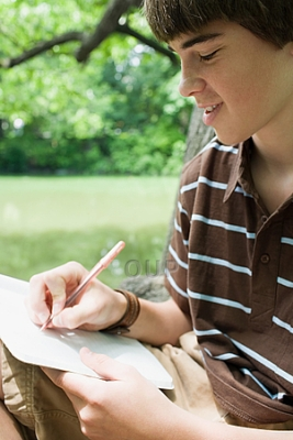 Boy writing on paper on the grass