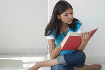 Asian girl sitting on the floor reading