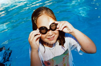 Girl in swimming pool with t-shirt and goggles