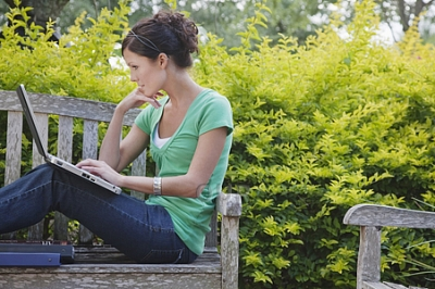 Young woman using laptop on park bench
