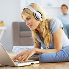 Woman on the floor with laptop and headset
