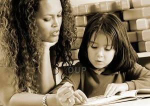 Woman teaching young girl to read