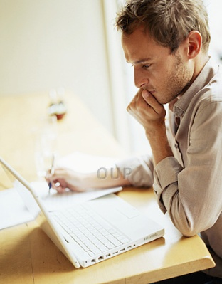 Young man thinking while using laptop