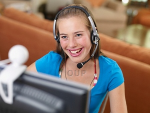 Girl with headset looking at computer monitor smiling