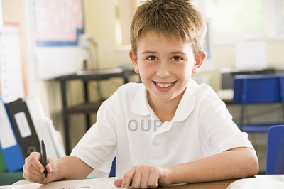 Young boy smiling and writing