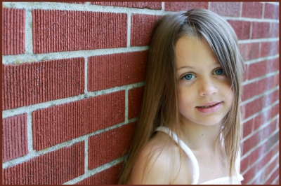 Young girl leaning against brick wall