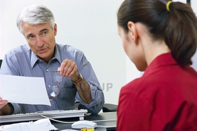 Older man interviewing young woman