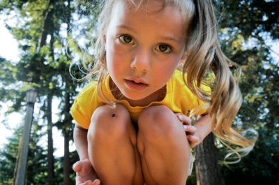 Curious child crouching in forest