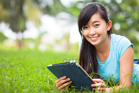 Girl in park with tablet computer